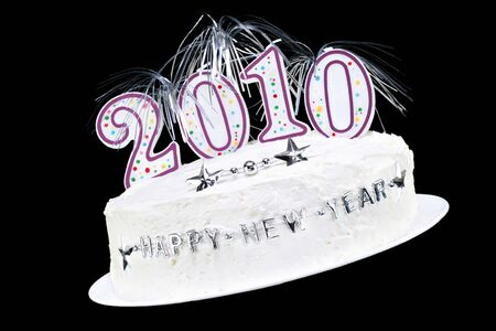 tilted view: White frosted Happy New Year Cake with 2010 candles and silver streamers.  Isolated on black with copy space. Stock Photo