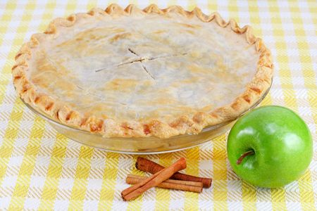 granny smith apple: One whole homemade apple pie with cinnamon sticks and a granny smith apple.