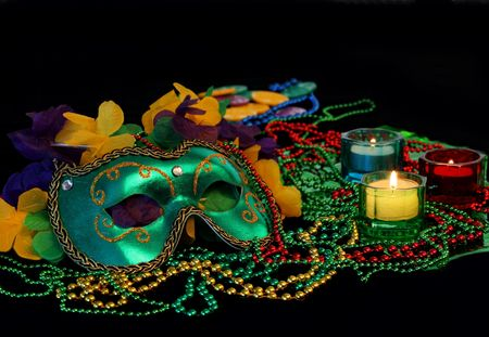 masquerade masks: Ingredients for Mardi Gras including a mask, beads and lit candles.  Low light evening image with copy space. Stock Photo