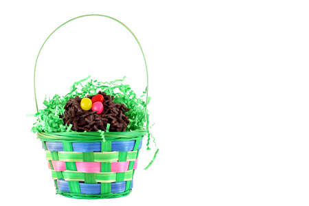 Colorful Easter basket with chocolate birds nest candy on white background with copy space. photo