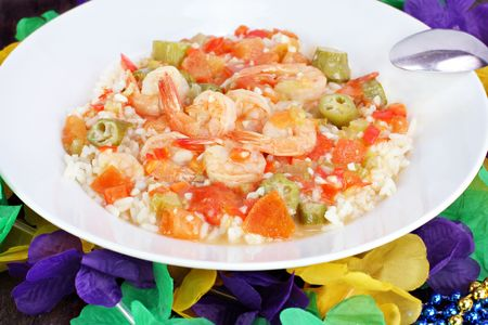 Shrimp Gumbo on white plate among Mardi Gras decorations.