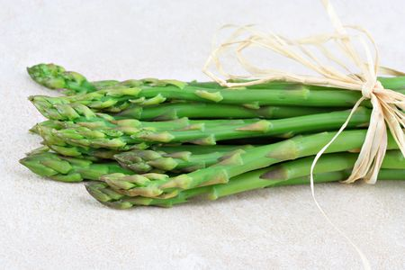 Fresh organic asparagus in a bunch tied with raffia on a tile counter top.  Selective focus on tips.  Copy space. Stock Photo - 6525441