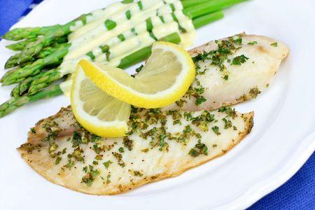 Freshly baked Tilapia fish dinner with fresh herbs and  healthy asparagus in Hollandaise sauce.  Lemon twirl for garnish.