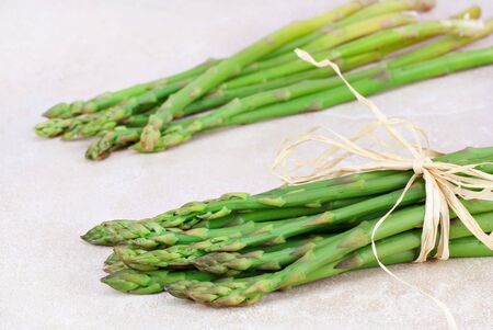 counter top: Two bunches of organic, fresh asparagus on a counter top. Stock Photo
