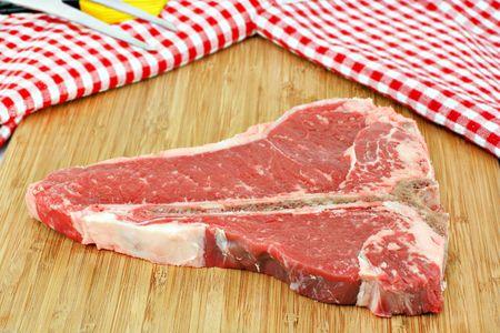 One fresh, raw porterhouse steak on a cutting board.