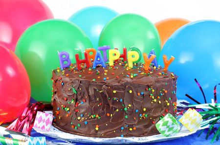 Chocolate cake decorated with Happy Birthday and surrounded with party poppers and streamers.  Colorful balloons in the background with copy space.