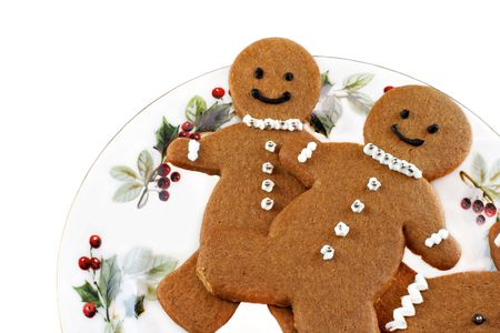 Decorated gingerbreadmen cookies on a pretty Christmas plate.  On white with copy space. Stock Photo