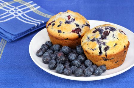 Delicous    Healthy fresh blueberries on a plate with fresh baked blueberry muffins.  Close up with copy space available. photo