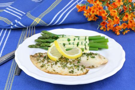 Healthy, fresh tilapia fillets with asparagus covered in Hollandaise sauce.