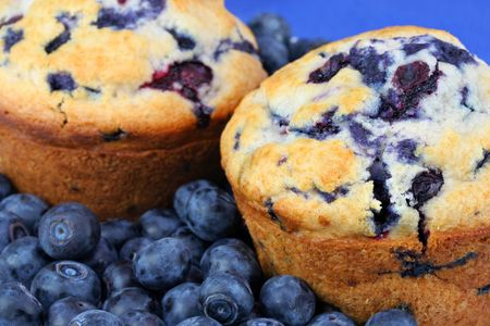 Two fresh baked blueberry muffins surrounded with fresh blueberries.  Extreme close up.