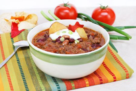 One bowl of Mexican Taco Soup, garnished with sour cream, scallions and vegetable chips. Stock Photo