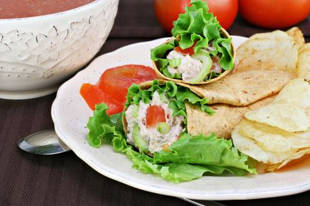 Healthy tuna salad wraps with a side of chips.  Bowl of tomato soup and fresh tomatoes in the background. photo
