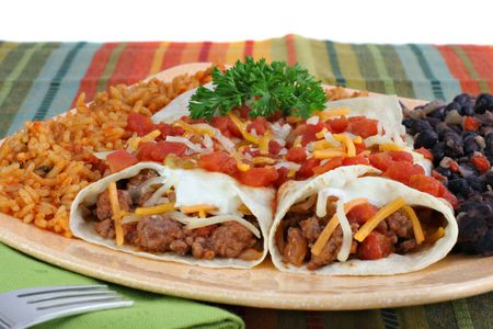 spanish food: Beef burrito dinner on a plate with Spanish rice and black beans.