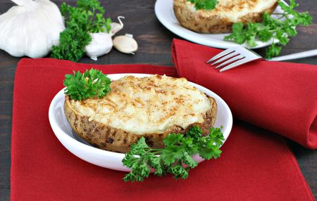 Twice baked stuffed garlic potatoes on a red napkin on a rustic wood table. Stock Photo - 6740503
