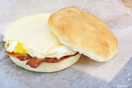 Bacon, egg and cheese sandwich on a homemade muffin.  Sandwich is on wax paper in to go fashion. photo