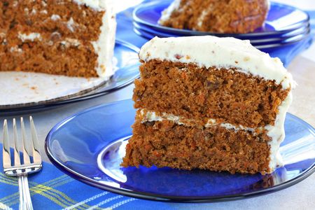 Delicious homemade carrot cake with cream cheese and nut frosting.  Sliced on blue glass plates with cut cake in background.