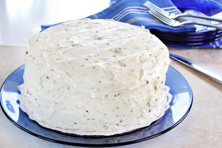 undecorated: One cream cheese and pecan frosted cake on a blue glass plate.  Natural window light.  Cake is undecorated. Stock Photo