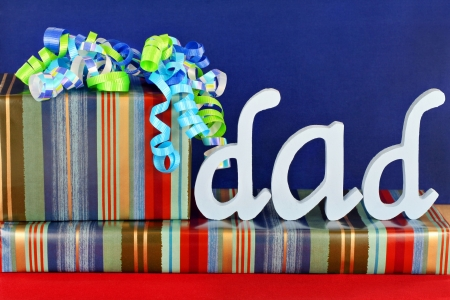 Masculine wrapped gifts with ribbons and the word Dad on top.  Ideal for dads birthday or fathers day. Stock Photo