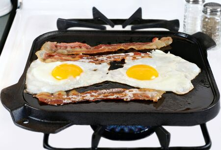 Two sunny side up eggs with bacon frying on a cast iron griddle, stove top with burner flame. photo