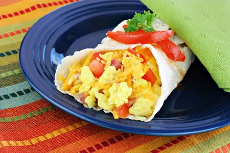 scrambled: Delicious breakfast egg, tomato, cheese and pepper burrito.
