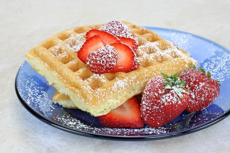 Homemade waffles on a blue glass plate topped with fresh strawberries and confectioners sugar. Stock Photo - 7002887