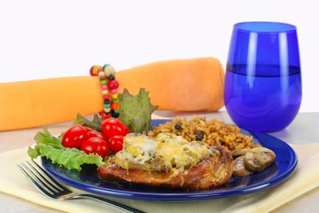 tex: Fiesta Tex Mex chicken with mushrooms and melted cheese.  Santa Fe rice and beans, grape tomatoes and lettuce as a side. Stock Photo