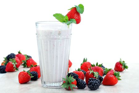 Strawberries and blackberries surround an fresh berry smoothie drink.  White background for copy space. Stock Photo - 7076394