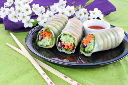 Healthy vegetable sushi on a black plate.  Spring setting with flowers in the background. photo