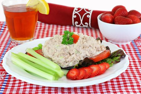 Fresh tuna salad on a plate with tomatoes, lettuce, celery and healthy strawberries. photo