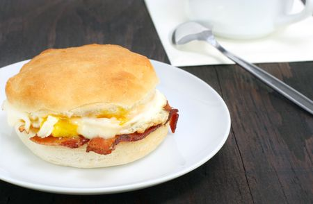 Fresh bacon and egg biscuit on a rustic wooden table.
