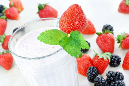 Delicious and fresh berry smoothie top view.  Strawberries and blackberries surround the glass. Stock Photo - 7152699