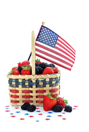 Patriotic basket full of fresh strawberries and blackberries.  Stars and a flag surround basket which is on white with copy space. Stock Photo - 7196001