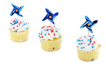 Three patriotic decorated cupcakes on a diagonal.  Red, white and blue with pinwheel decorations. photo
