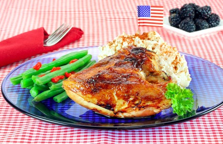 Barbecued chicken, fresh potato salad, organic string beans with american flag garnish. Stock Photo