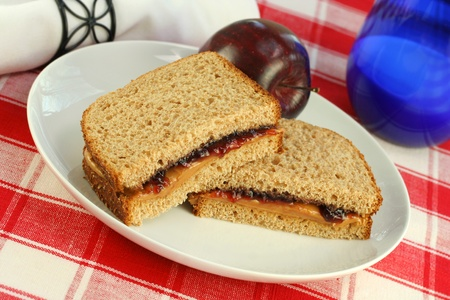 One cut peanut butter and jelly sandwich on wheat grain bread.