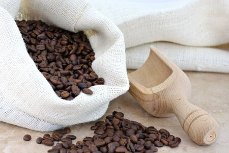 abundant: A burlap sack of fresh coffee beans with a wooden scoop to the side. Stock Photo