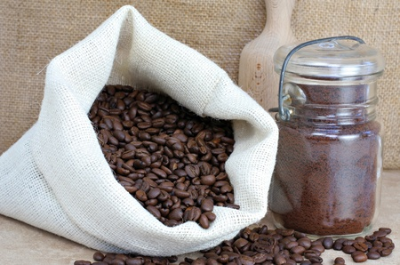 Fresh coffee beans in a beige colored sack next to a lidded jar of ground coffee. photo