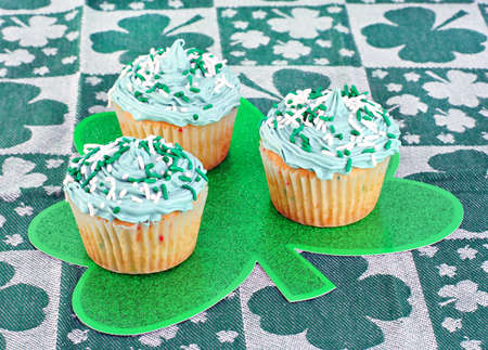 Three festive cupcakes for St. Paddys day on a shamrock.  Selective focus on front cupcake. photo