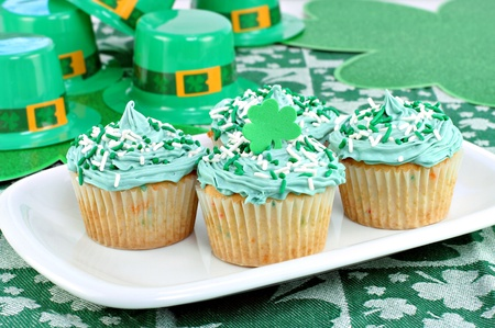 Four decorated cupcakes in a festive St. Patricks day setting with shamrocks and fedoras. Stock Photo
