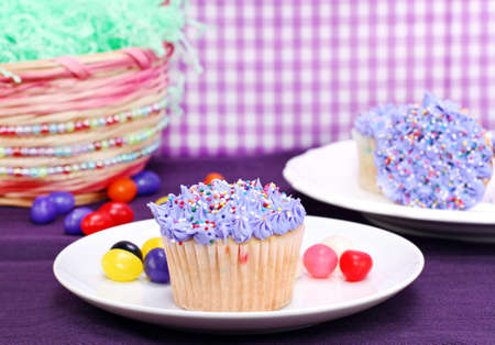 Easter cupcakes, jelly beans and an Easter basket. photo