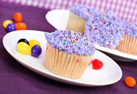 Selective focus on one pretty purple cupcake with jelly beans scattered. Stock Photo