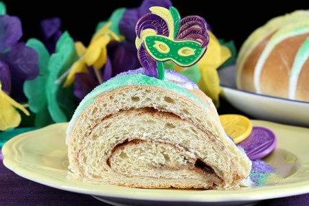 spice cake: One slice of Kings Cake on a yellow plate with Mardi Gras decorations. Stock Photo
