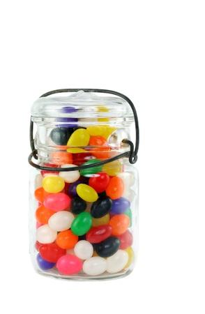 Vintage mason jar full of colorful jelly beans on white. Foto de archivo