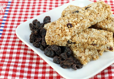 Healthy raisin and nut granola bars stacked on a plate.