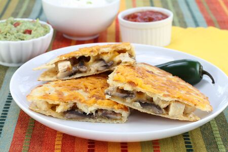 One chicken, mushroom and cheese Quesadilla on a plate with complimentary sauces to the side.