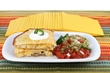 dollop: Stacked chicken, cheese and mushroom quesadilla with a dollop of sour cream.  Sides of guacamole, jalapino slices, and salsa.