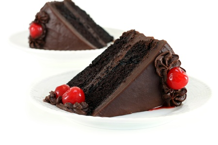 Chocolate Fudge Cake with Chocolate Frosting and Cherries for garnish on a white table.  Selective focus on front piece.