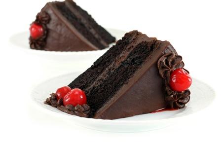 trozo de pastel: Pastel de Fudge chocolate con Chocolate Frosting y cerezas para adornar sobre una mesa blanca.  Enfoque selectivo en la parte frontal.