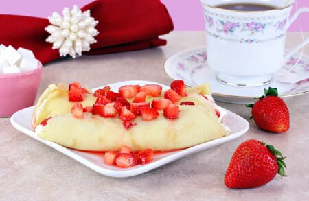 Delicate and delicious strawberry crepes set in a feminine table setting.  Appropriate for Moms birthday or Mothers Day. Banco de Imagens