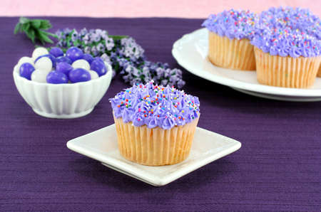 Pretty cupcakes with sprinkles and purple icing on a table with jelly beans for Easter. Stock Photo - 9227787